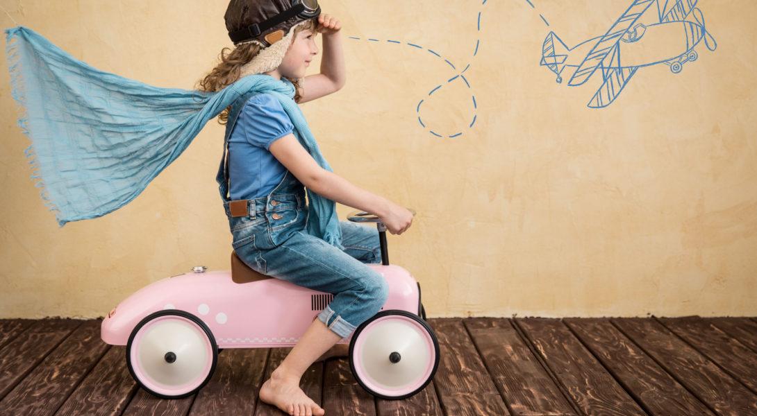 Petite fille qui joue chez elle sur une petite voiture rose à imaginer voyager