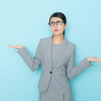 Avocate féminine élégante posant devant un fond bleu ciel avec une expression de confusion