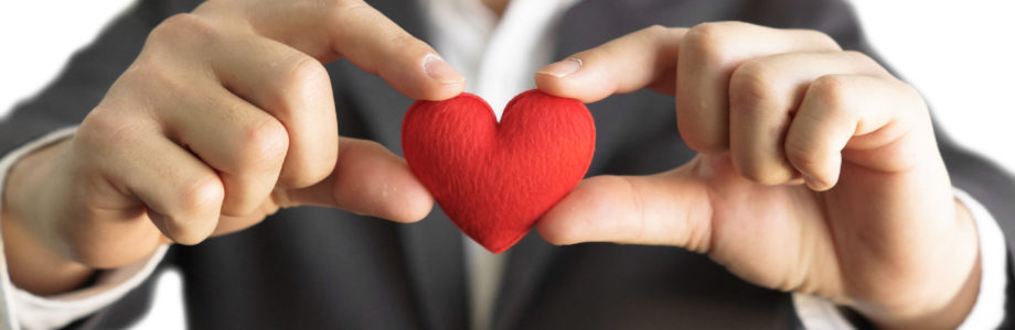 homme d'affaire qui tient entre ses doigts un coeur rouge en tissu